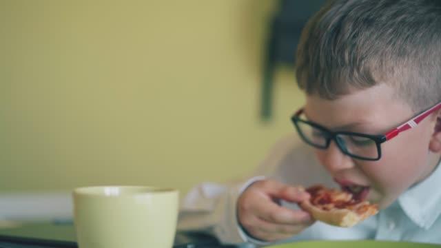 stockvideo's en b-roll-footage met de leerling eet plak van verse pizza bij kop op lijst in kantine - dikke pizza close up