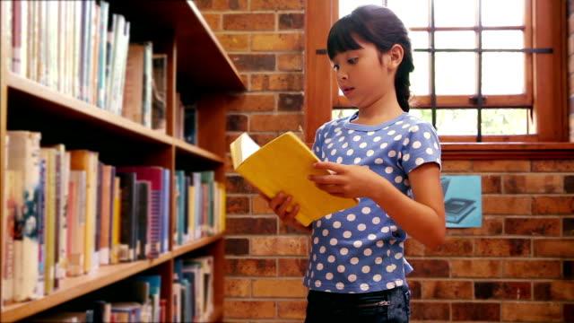 stockvideo's en b-roll-footage met pupil taking book from shelf at the library - boekenkast