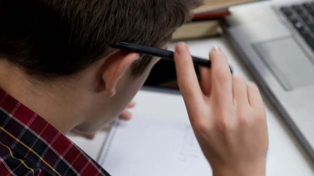 Pupil thinking over difficult homework, writing exercise in notebook, back view video