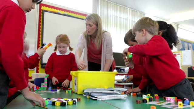 Pupils And Teacher Tidying Up Coloured Blocks video