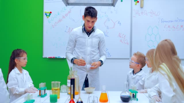 Pupils and teacher watching experiment in science class video