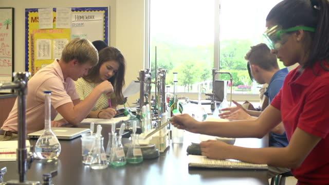 vídeos y material grabado en eventos de stock de realizar el experimento alumnos en clase de ciencias - deportes de la escuela secundaria