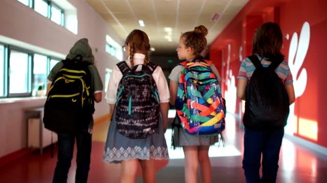 學生們穿過學校的走廊。兩個男孩和兩個女孩孩子們背著背包。回學校去後視圖 - back to school 個影片檔及 b 捲影像