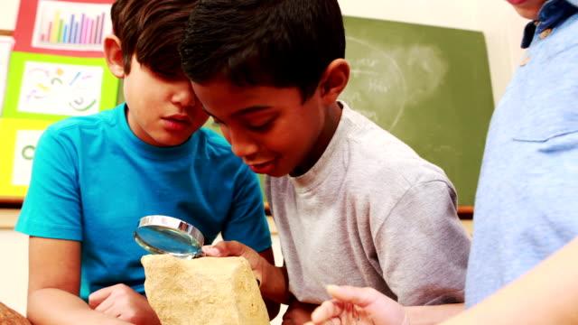 stockvideo's en b-roll-footage met leerlingen kijken naar rock met vergrootglas - geologie