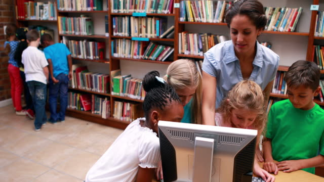 Pupils looking at the computer in library with their teacher video