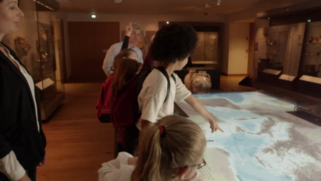 pupils on school trip to museum looking at map shot on r3d - viaggio d'istruzione video stock e b–roll