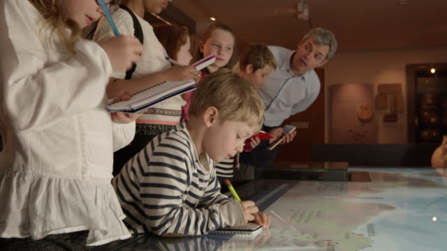 pupils on school trip to museum looking at map shot on r3d - museo video stock e b–roll