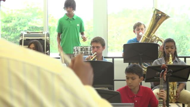 учащиеся играют музыкальные инструменты в школе оркестр - class стоковые видео и кадры b-roll
