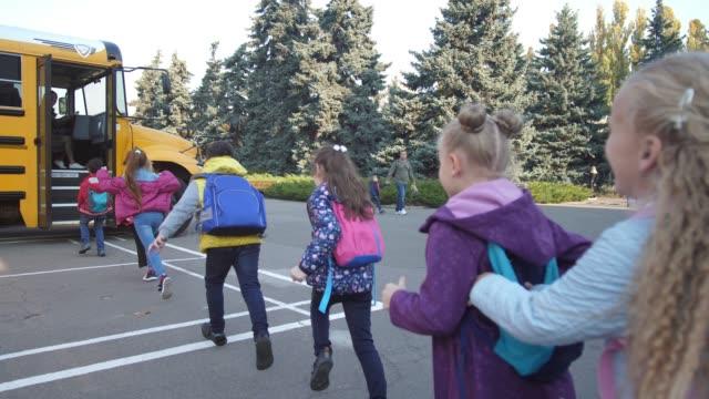 vídeos y material grabado en eventos de stock de alumnos regocijándose al final de las lecciones corriendo al autobús - autobuses escolares