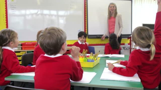 vidéos et rushes de les élèves assis autour de table enseignant pose une question - uniforme