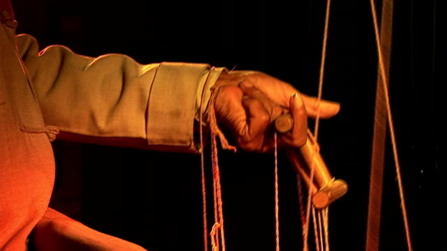 puppet 2 close up: hand leads puppet strings marionette stock videos & royalty-free footage