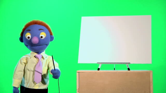 Puppet Businessman Points To Blank White Chart HD720p: Well dressed businessman puppet explains something using a blank white chart and pointer.  Medium Wide isolated on a green background. marionette stock videos & royalty-free footage