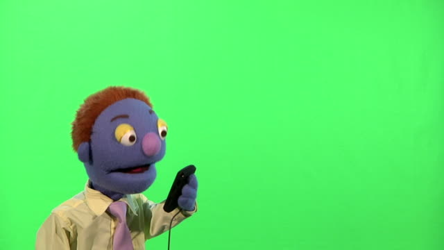 Puppet Businessman Talks On Cell Phone HD720p:  Well dressed businessman puppet answers cell phone, has a conversation and hangs up.  Medium shot isolated on a green background. salesman stock videos & royalty-free footage