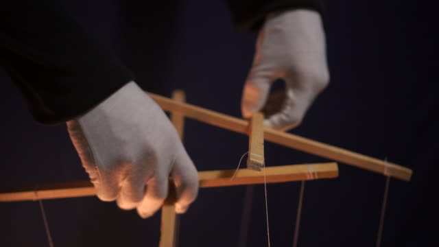 Puppet theatre. Manipulating A Marionette By A Puppeteer. Isolated, black background