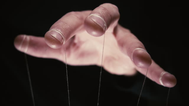 Puppeteer with manipulating hands controlling all your moves. Concept We are being manipulated concept. Large scary hands with puppet string tied around fingers marionette stock videos & royalty-free footage