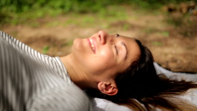 Pure joy in nature Woman lying down on the blanket in nature,resting and smiling human joint stock videos & royalty-free footage