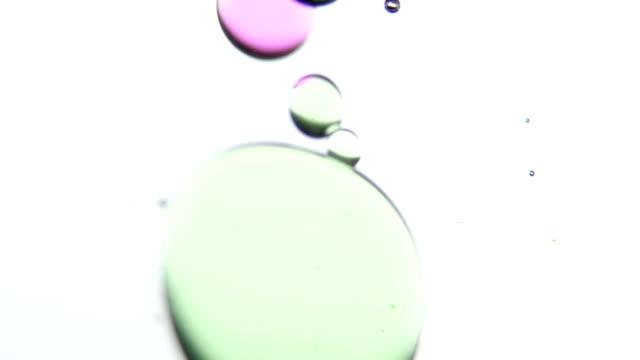 vídeos de stock e filmes b-roll de roxo e verde acrílico gotas. intervalo de tempo. branco. plano aproximado - oleo palma