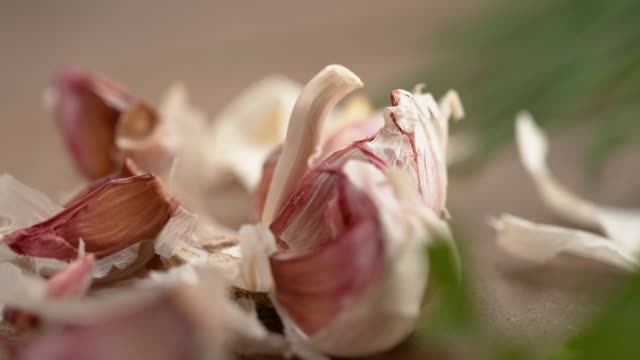 slow motion purple cloves of garlic get scattered after falling on kitchen table - aglio alliacee video stock e b–roll