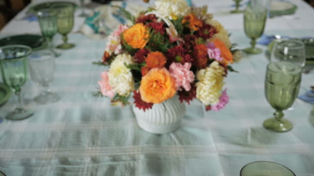 Encaje un presión de una pieza centro de flores en una gran mesa de comedor. - vídeo
