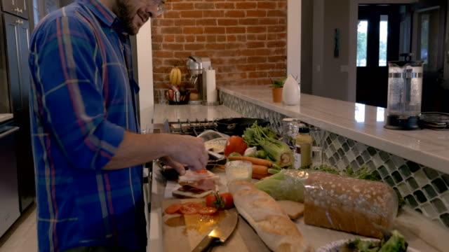 schieben sie in einem mann setzen geschnittene tomaten und salat auf einem sandwich - vollkorn stock-videos und b-roll-filmmaterial