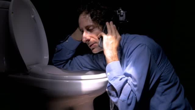 stockvideo's en b-roll-footage met duw binnen van een mensenzitting op de vloer tegen een toilet op een telefoon - cell phone toilet