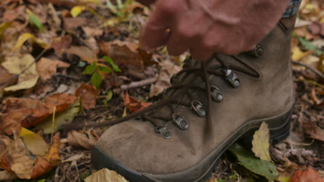 vídeos de stock e filmes b-roll de push in of a man tying his hiking boots and then walking away in the forest - bota