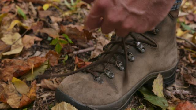 spingere in di un uomo legare i suoi stivali da trekking e poi a piedi nella foresta - annodare video stock e b–roll