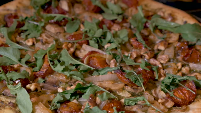 push in of a vegan pizza with arugula, walnuts, roasted tomatoes and onions - pinolo video stock e b–roll
