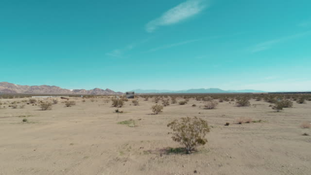 Push in of an american desert valley on a sunny day AERIAL - Drone moves forward in the sandy Mojave desert on a clear blue day while crossing some tumbleweed mojave desert stock videos & royalty-free footage