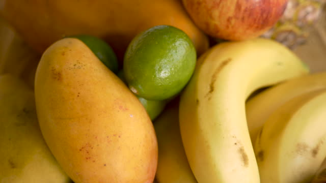 Push in of limes, bananas, mangoes, apples and other fruit