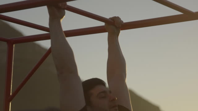 Push up exercises Man doing push ups on exercise poles in the nature during the sunset bodyweight training stock videos & royalty-free footage