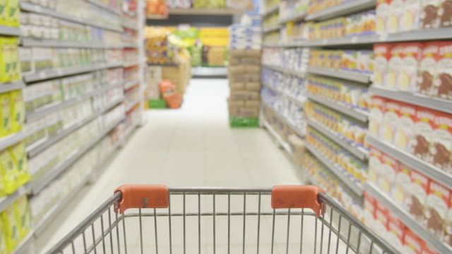 pushing a shopping cart in supermarket - dolly shot video stock e b–roll