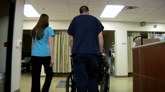 Pushing Patient In WheelChair Medical personnel pushing patient in wheelchair. pushing wheelchair stock videos & royalty-free footage
