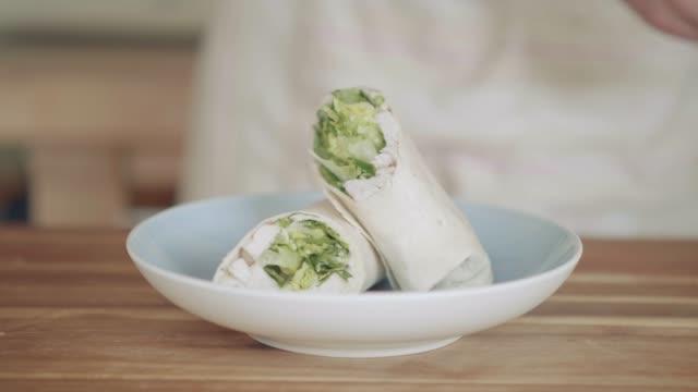 sätta kyckling caesar sallad wrap smörgås på plattan - cheese sandwich bildbanksvideor och videomaterial från bakom kulisserna