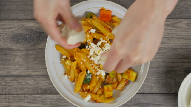put feta cheese on vegetable pasta salad into a salad bowl - melanzane video stock e b–roll