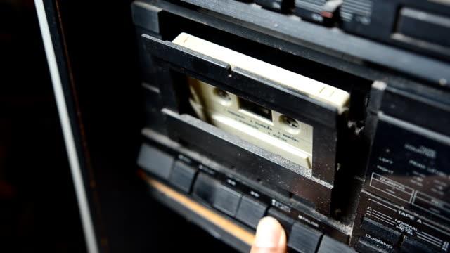 metti in una vecchia cassetta registratore ligt in basso - mangianastri video stock e b–roll