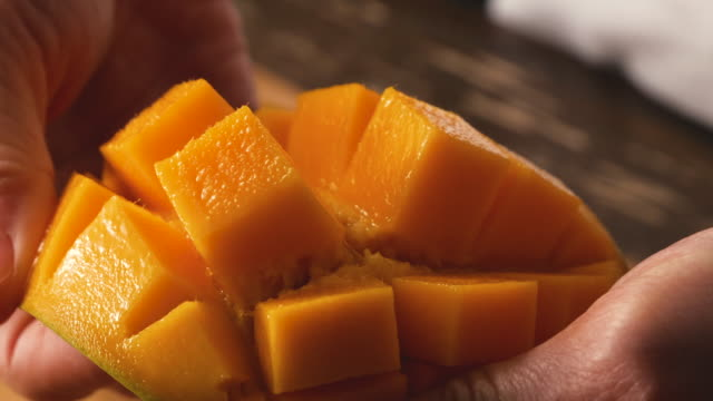 Put out the cut mango fruit. The mango fruit is cut in a grid pattern. mango stock videos & royalty-free footage