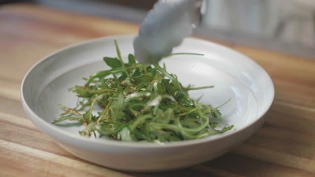 put summer rocket leaves salad into bowl