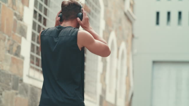 Put your beats and workout on blast 4k video footage of a fit young man using headphones during a workout in the city sportsperson stock videos & royalty-free footage