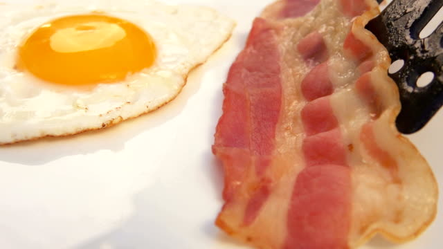 puts bacon on a white plate with eggs Cook puts bacon on a white plate with eggs bacon stock videos & royalty-free footage