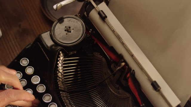 DS putting a paper sheet into old typewriter Right above medium dolly shot of person siting behind an old office desk putting a new sheet of paper into an old typewriter. typewriter stock videos & royalty-free footage