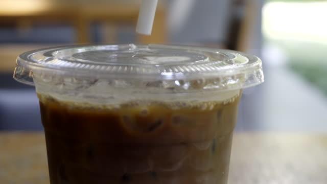putting a plastic straw to coffee - coperchio video stock e b–roll