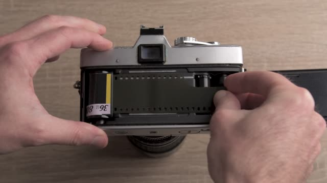 Putting a roll of photography film in the camera