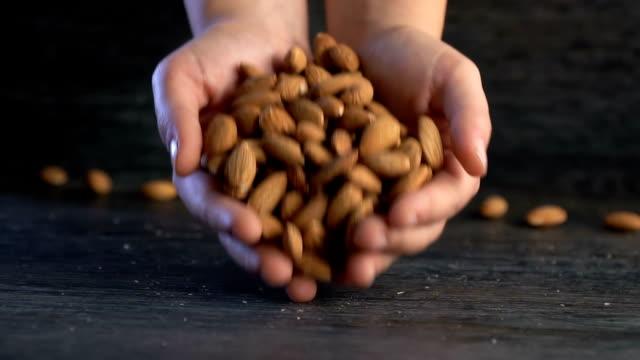 vídeos de stock e filmes b-roll de putting almond on the wooden table - amendoas