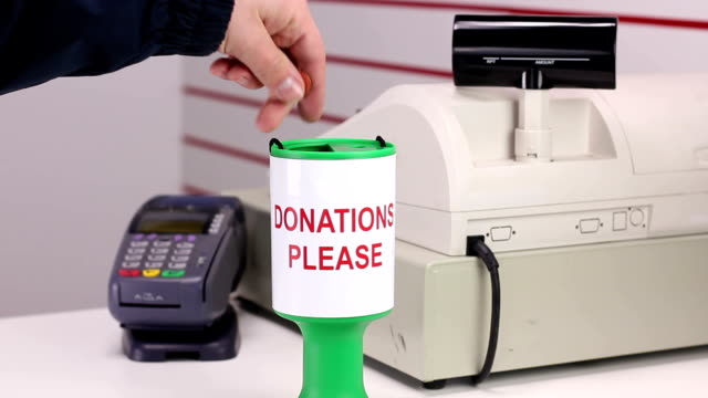 Putting coins into Charity Donation Box by till video