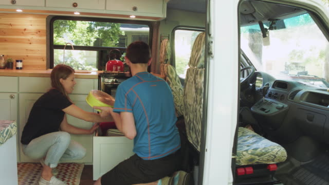 Putting dishes away in the van A young couple who live in a van are putting the dishes away rv interior stock videos & royalty-free footage