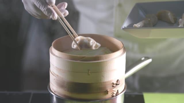 Putting dumplings into a bamboo steamer box