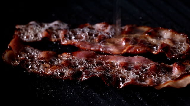 Putting Eggs For Frying Near Of Two Slices Of Bacon On Grill Putting Eggs For Frying Near Of Two Slices Of Bacon On Grill Pan bacon stock videos & royalty-free footage