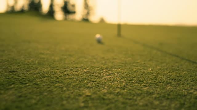 putting golf ball auf grün in golfplatz schlagen den golfball zu loch für birdie-score, sport entspannen in urlaub sommerurlaub bei sonnenuntergang goldene zeit, filmische zeitlupe nfootage - golf stock-videos und b-roll-filmmaterial