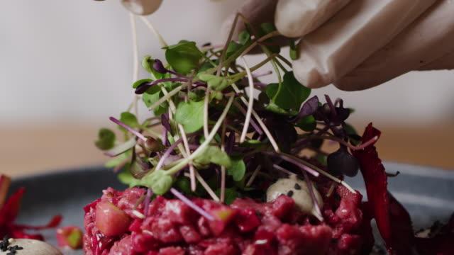 putting greenery on beef tar tar macro - tajska kuchnia filmów i materiałów b-roll